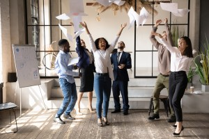 Picture of Funny happy multiracial corporate team people dancing toss papers