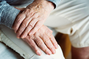 elderly person sitting with both hands on right knee