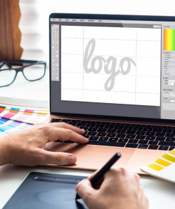 graphic designer working at a laptop and using a drawing tablet